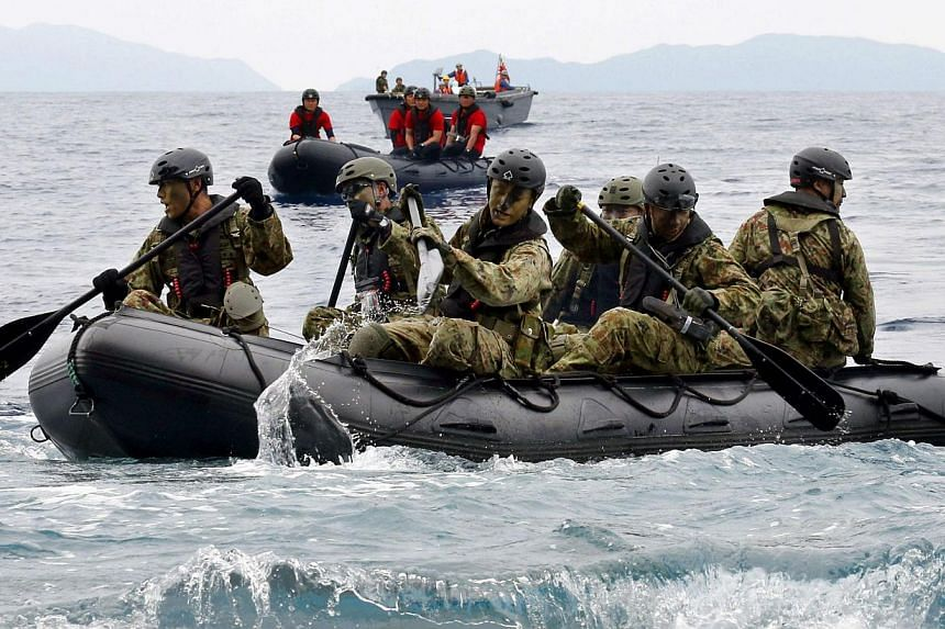 Japan Self-Defense Force (JSDF) soldiers travelling in a rubber boat on the sea approach Eniyabanare Island from JSDF transport vessel Shimokita during a military drill, off Setouchi town on the southern Japanese island of Amami Oshima, Kagoshima pre