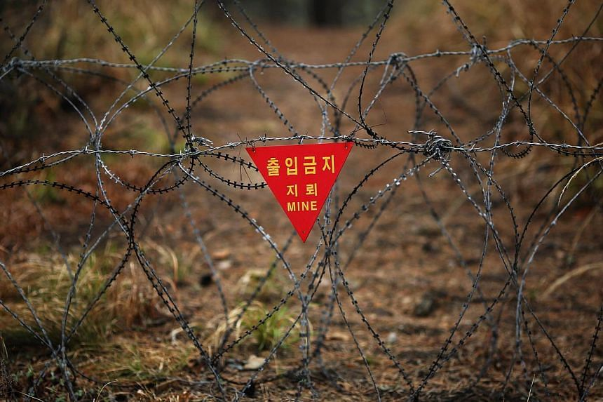 A warning sign hangs on razor wire on the island of Baengnyeong, which lies on the South Korean side of the Northern Limit Line (NLL), in the Yellow Sea in this April 12, 2014 file photograph. North Korea made a surprise proposal on Monday that the t