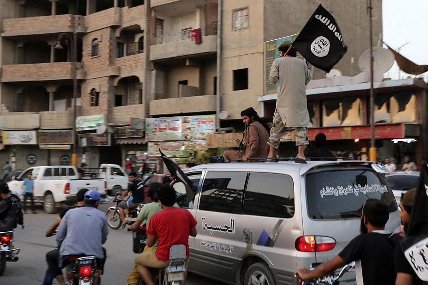 Members loyal to the Islamic State in Iraq and the Levant (ISIL) wave ISIL flags as they drive around Raqqa on June 29, 2014. -- PHOTO: REUTERS
