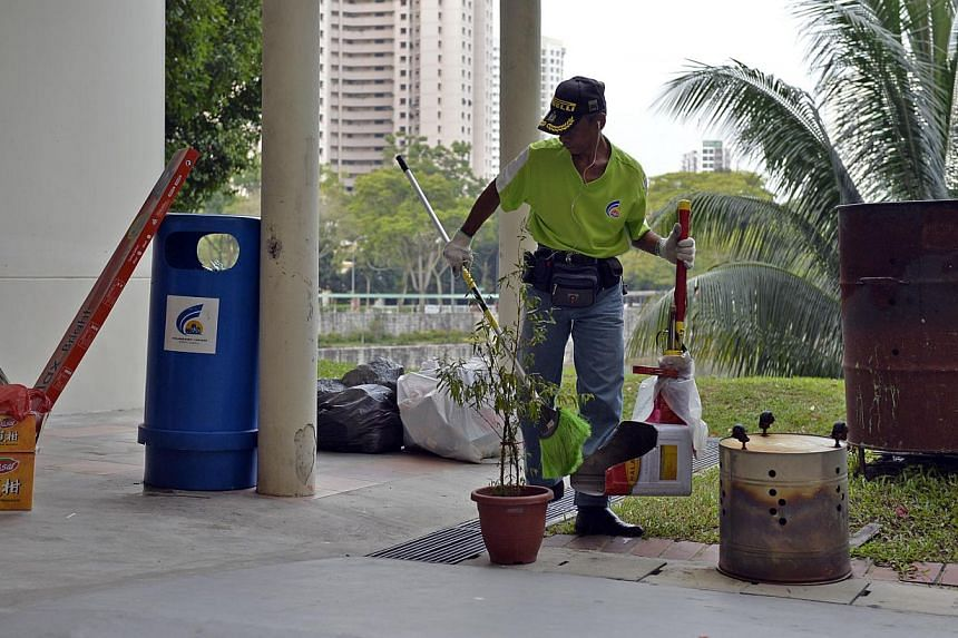 A cleaner sweeping and clearing rubbish at the void deck of a HDB flat at Bukit Panjang. -- PHOTO: ST FILE
