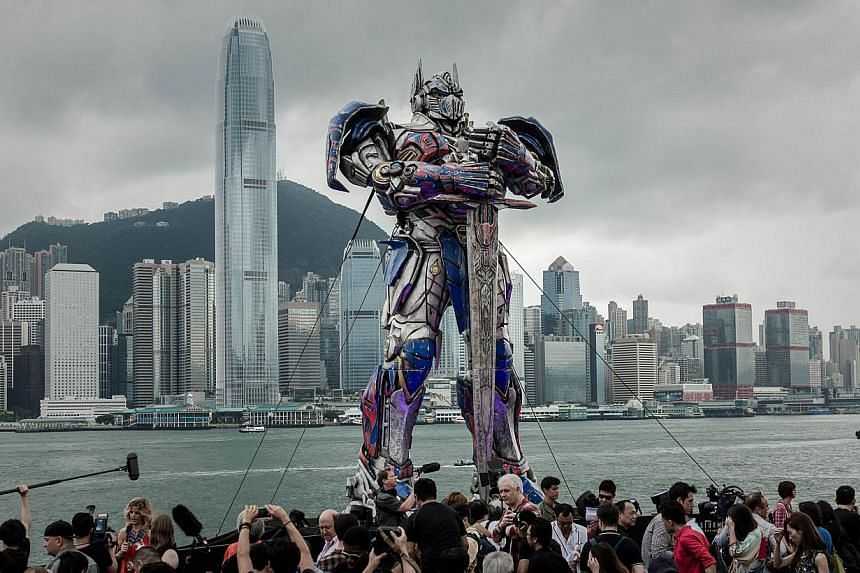 A 20 foot-tall Optimus Prime figure is surrounded by journalists before the world premiere of Hollywood movie Transformers 4 in Hong Kong on June 19, 2014.Transformers: Age Of Extinction, the fourth in the series of films about form-changing Au