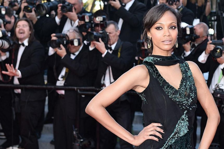 US actress Zoe Saldana poses as she arrives for the screening of the film Mr Turner at the 67th edition of the Cannes Film Festival in Cannes, southern France, on May 15, 2014. The Avatar star will be here from July 10 to 12 to promote her new movie,