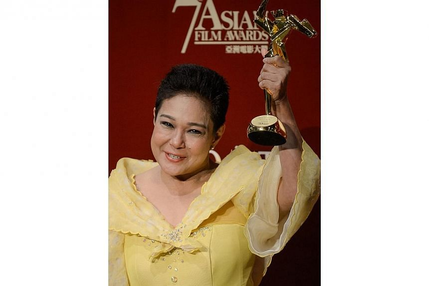This file photo taken on March 18, 2013 shows Philippine actress Nora Aunor posing with the Best Actress Award at the 7th Asian Film Awards in Hong Kong.Philippines President Benigno Aquino on Tuesday defended a controversial decision he made t
