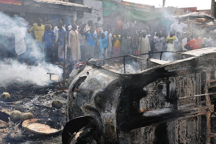 People gather to look at a burnt vehicle following a bomb explosion that rocked the busiest roundabout near the crowded Monday Market in Maiduguri, Borno State, on July 1, 2014.A truck exploded in a huge fireball killing at least 15 people on T