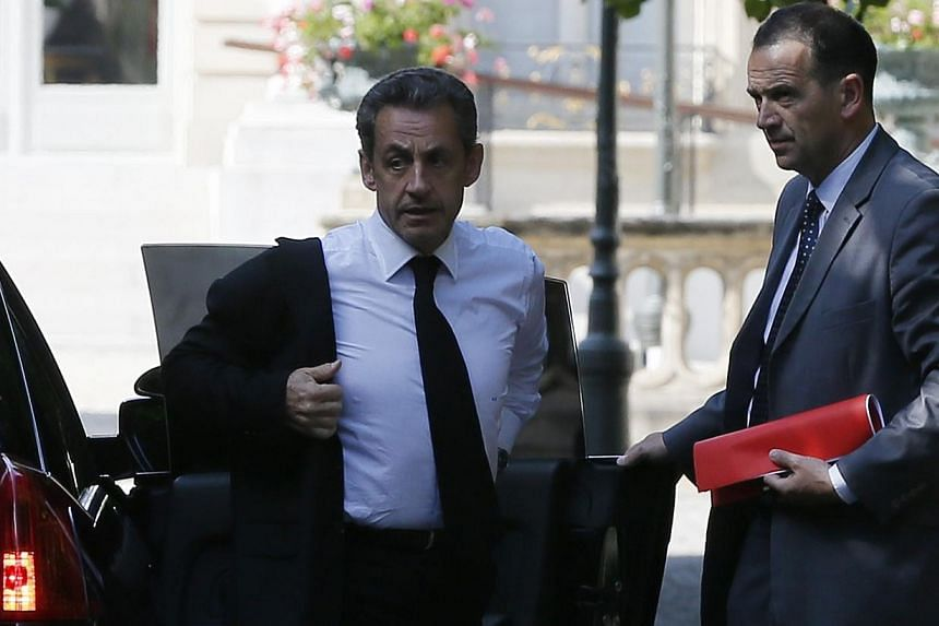 Former French President Nicolas Sarkozy (left) arrives at the National Assembly in Paris June 25, 2014.Mr Sarkozy was on Tuesday, June 1, 2014, detained for questioning in a widening corruption probe, a judicial source told AFP, in an unprecede