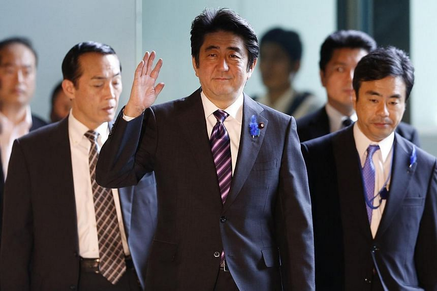 Japan's Prime Minister Shinzo Abe (centre) waves upon his arrival at his official residence in Tokyo July 1, 2014. Japan on Tuesday loosened restrictions on its powerful military, allowing it to go into battle in defence of allies, in a major an