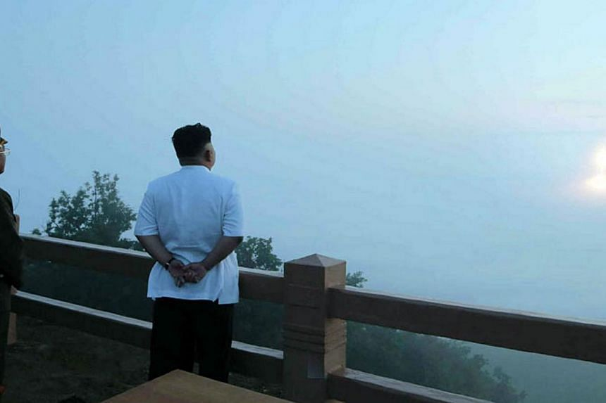 This undated picture released from North Korea's official Korean Central News Agency on June 30, 2014 shows North Korean leader Kim Jong-Un (right) observing a tactical rocket launch by the Korean People's Army Strategic Force at an undisclosed place