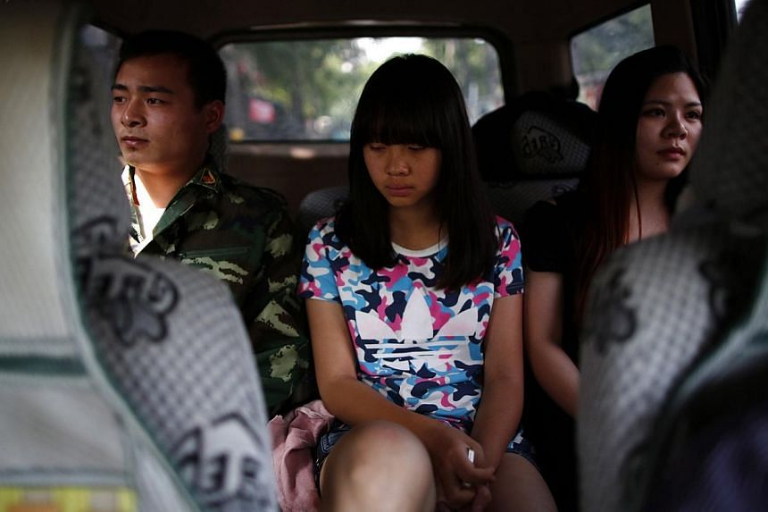 A female teacher and an instructor who is an ex-soldier, escort a girl in a car as they take her to the Qide Education Center at the request of her parents in Beijing on May 22, 2014. -- PHOTO: REUTERS