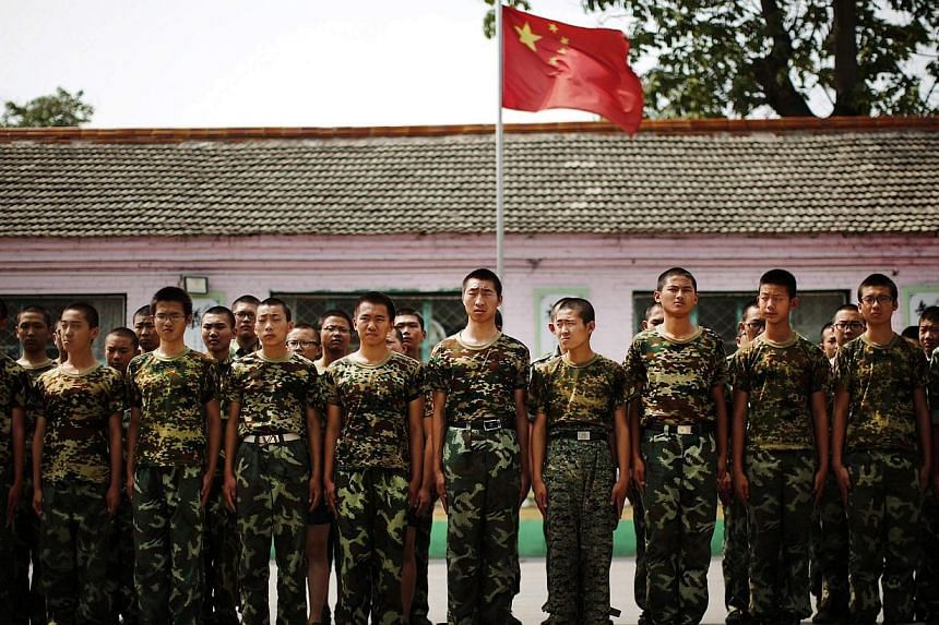 Students stand in front of the Chinese national flag as they prepare to take part in a military drill at the Qide Education Center in Beijing on June 11, 2014. -- PHOTO: REUTERS