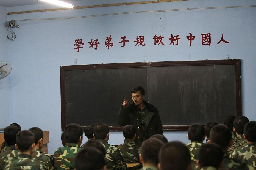 An ex-military instructor teaches students during their the evening roll call at the Qide Education Center in Beijing on Feb 26, 2014. -- PHOTO: REUTERS