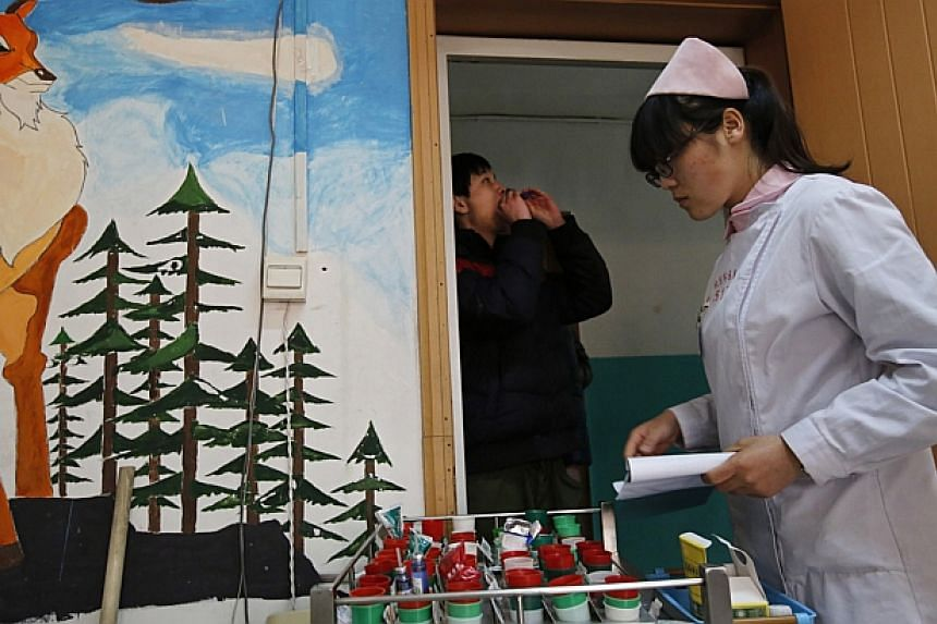 A nurse distributes medicine at Daxing Internet Addiction Treatment Center in Beijing on Feb 22, 2014. -- PHOTO: REUTERS