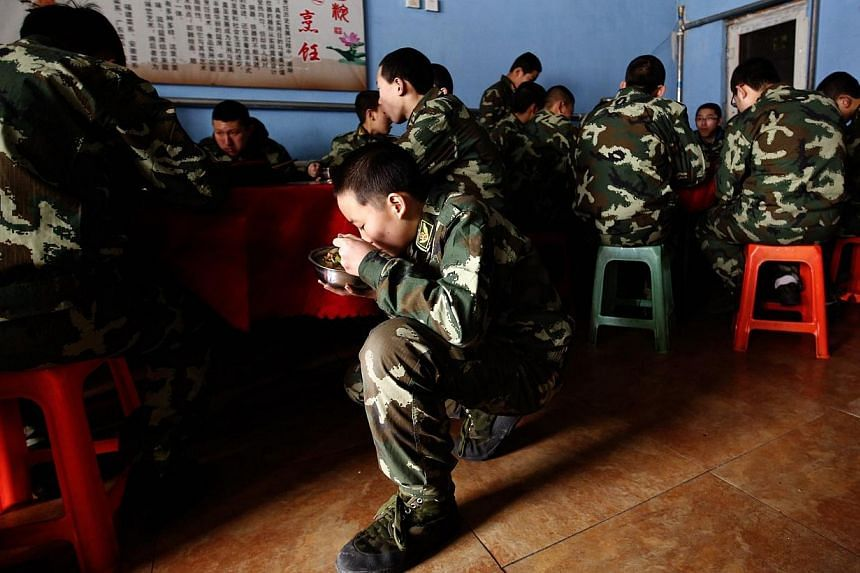 Students eat a meal at the Qide Education Center in Beijing on Feb 19, 2014. -- PHOTO: REUTERS