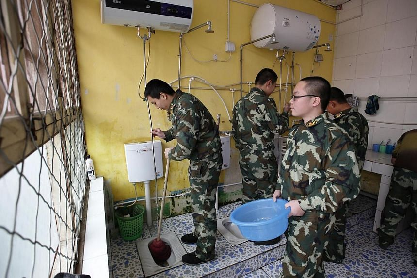 Wang (left), who was addicted to internet gaming, helps clean a bathroom in his dormitory at the Qide Education Center in Beijing on Feb 19, 2014. -- PHOTO: REUTERS