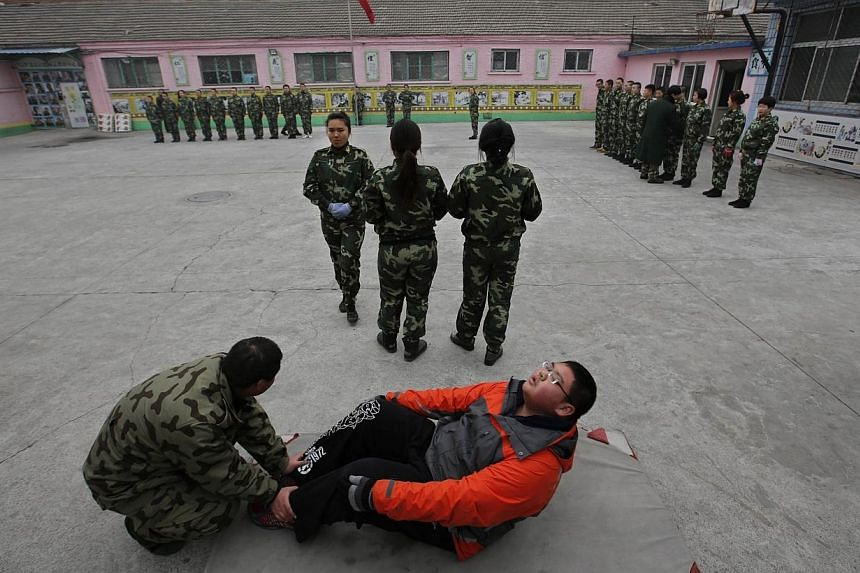 A new student (front) practices sits-up while other students take part in a close-order drill at the Qide Education Center in Beijing on Feb 26, 2014. -- PHOTO: REUTERS