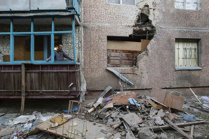A man looks out of a window of an apartment damaged by shelling in Slaviansk in eastern Ukraine on June 30, 2014.Ukrainian government forces launched air strikes and artillery assaults on pro-Russian separatists in eastern regions on Tuesday, J