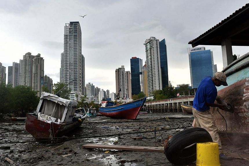 A fisherman repairs his boat at Panama City's Boca La Caja neighbourhood on April 25, 2014. -- PHOTO: AFP
