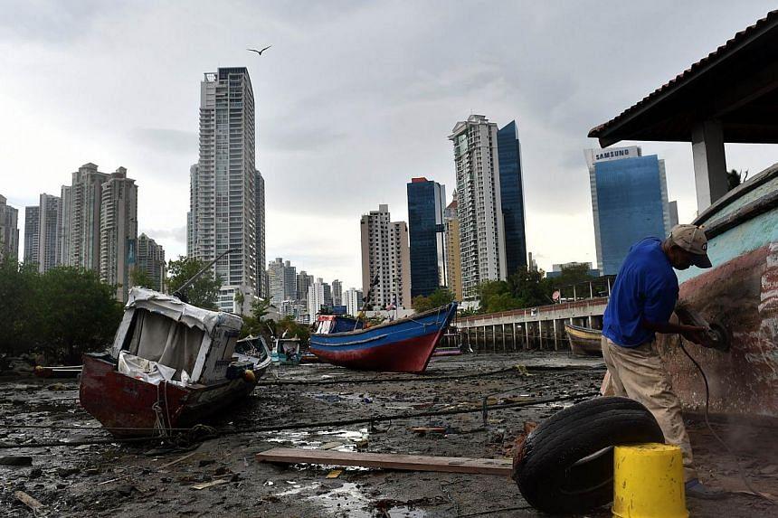 A fisherman repairs his boat at Panama City's Boca La Caja neighbourhood on April 25, 2014. -- PHOTO: AFP