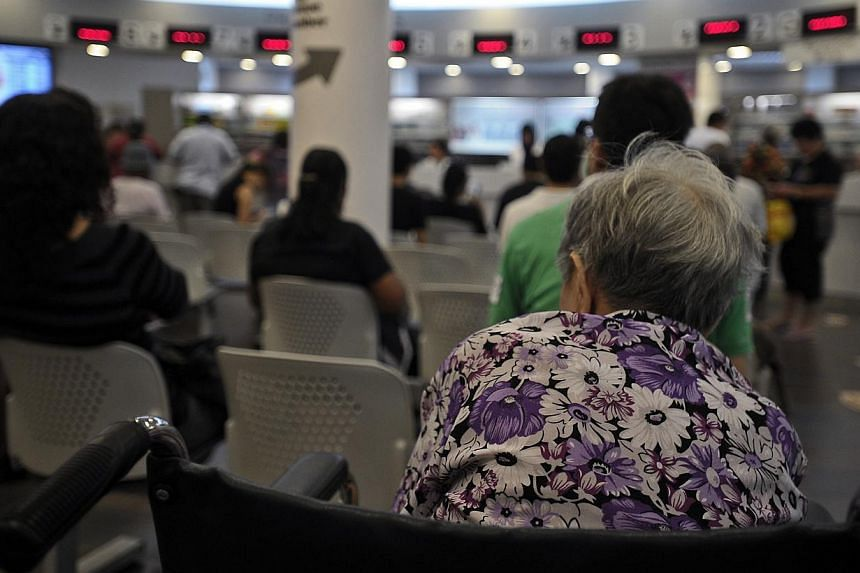 An elderly woman sits in the Pharmacy waiting area of Choa Chu Kang Polyclinic. -- PHOTO: JOSEPH NAIR FOR THE STRAITS TIMES