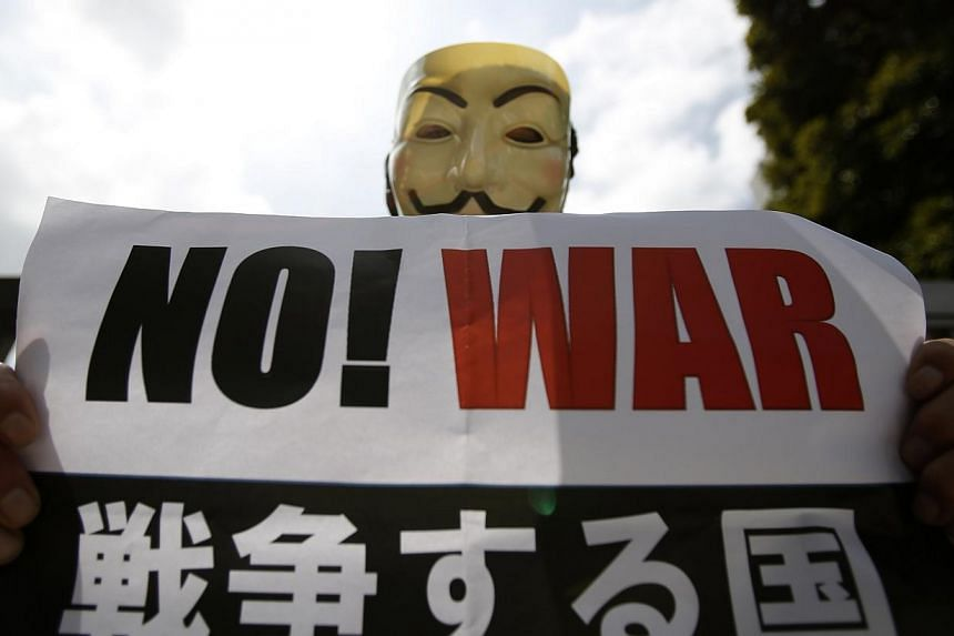 A protester wearing a mask holds a placard at a rally against Japan's Prime Minister Shinzo Abe's push to expand Japan's military role in front of Abe's official residence in Tokyo on July 1, 2014. -- PHOTO: REUTERS