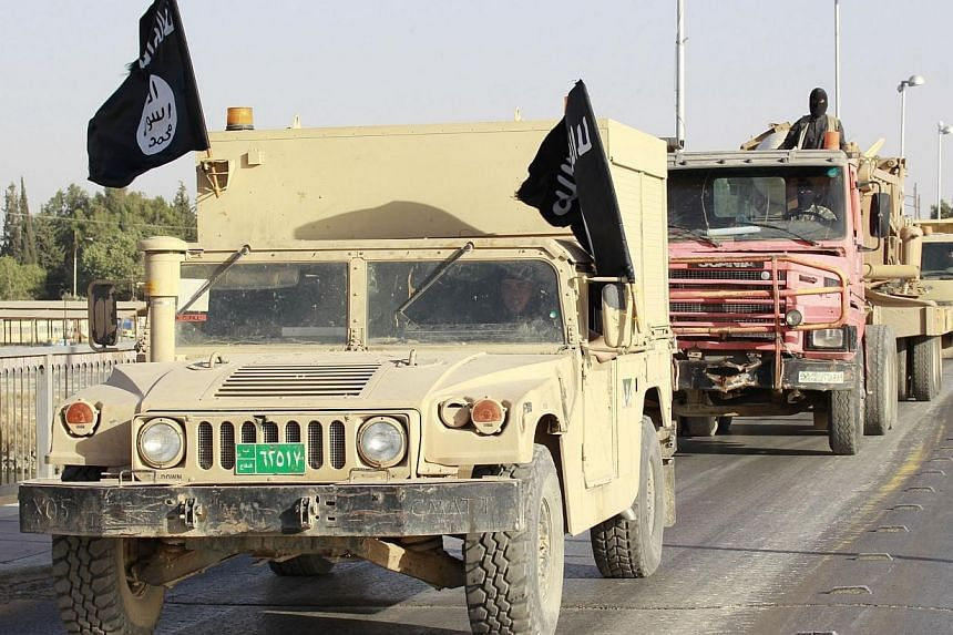 Militant Islamist fighters in military vehicles parade along the streets of Syria's northern Raqqa province on June 30, 2014.Syrian rebels, including the main Islamist factions, said on Monday the creation of a caliphate by the Islamic State (I