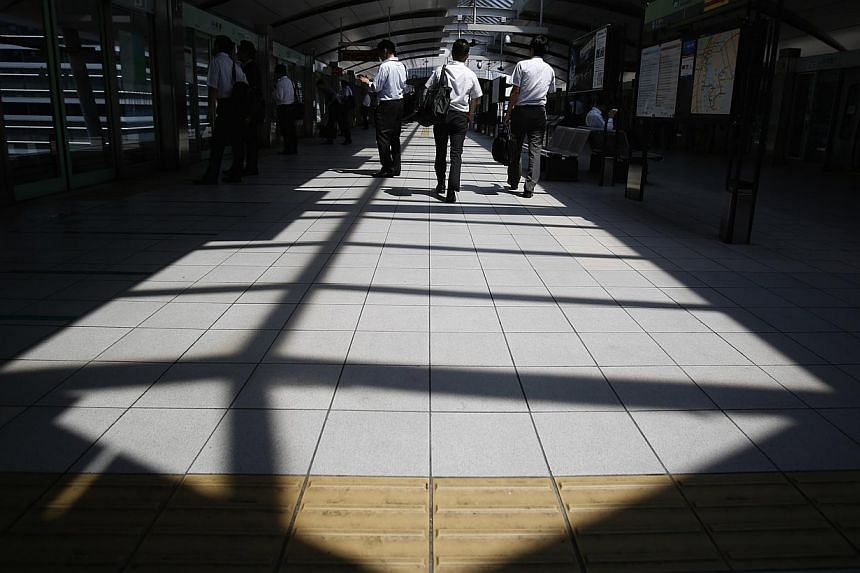 People walk on a platform of a train station at a business district in Tokyo June 19, 2014. -- PHOTO: REUTERS