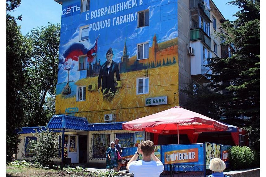 Pedestrians walk by a mural depicting Russian president Vladimir Putin dressed as a Russian Navy seaman, in the Crimean city of Sevastopol, on June 28, 2014.Russia plans to issue a banknote dedicated to Crimea, a senior central bank official sa