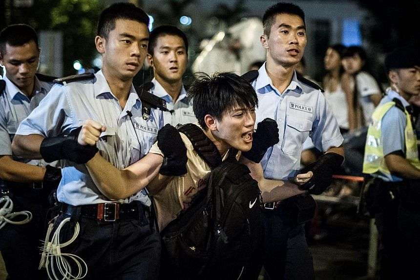 Policemen remove protesters in the central district after a pro-democracy rally seeking greater democracy in Hong Kong early on July 2, 2014 as frustration grows over the influence of Beijing on the city. -- PHOTO: AFP