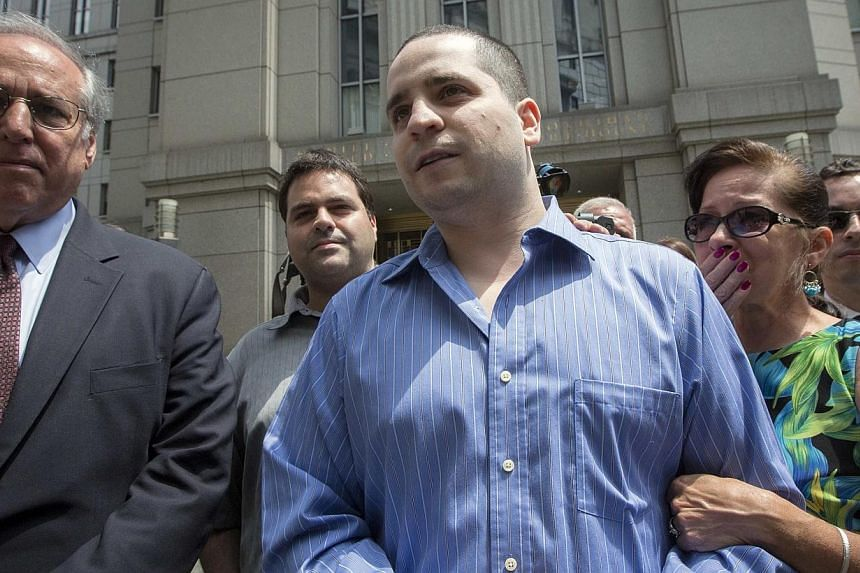 """Former New York City police officer Gilberto Valle (centre), dubbed by local media as the """"Cannibal Cop,"""" leaves the US District Court for the Southern District of New York in Lower Manhattan, July 1, 2014. -- PHOTO: REUTERS"""