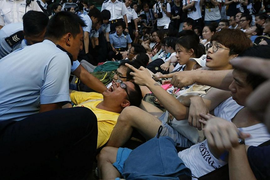 A protester (L) reacts as others shout at police officers as they take him away from a street after staying overnight at Hong Kong's financial Central district on July 2, 2014. Pro-democracy protesters gathered for a mass march in Hong Kong on July 1