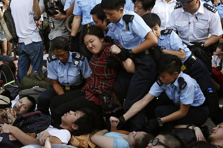 A protester reacts as she is dragged away by police officers on a street outside HSBC headquarters at Hong Kong's financial Central district on Wednesday, July 2, 2014, after an overnight sit-in with fellow demonstrators, at a mass rally demanding gr