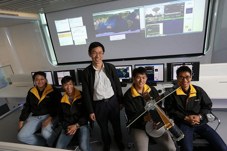 Director of NTU Satellite Research Centre Assoc Prof Low Kay Soon (centre, standing) with some of his students who built the VELOX-I. Locally-built satellites VELOX-I and VELOX-PIII were launched into space by a rocket from India at 12.21pm Sing