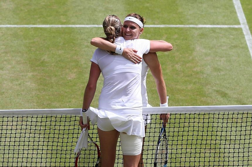 Czech Republic's Petra Kvitova (front) hugs her country woman Czech Republic's Lucie Safarova after the former won their women's singles semi-final match on day ten of the 2014 Wimbledon Championships at The All England Tennis Club in Wimbledon, sout