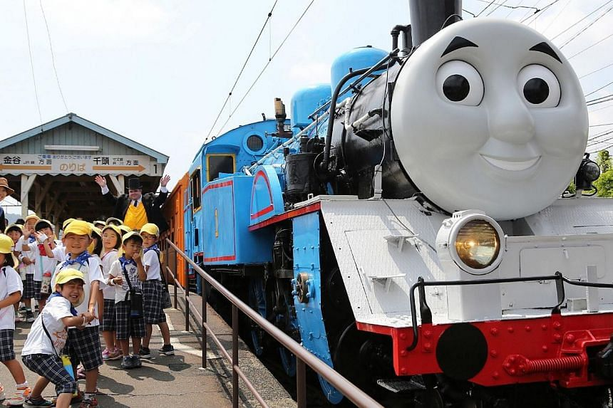 A life-sized Thomas the Tank Engine, surrounded by young schoolchildren at Shinkanaya station along Japan's Oigawa railway, in the city of Shimada in Shizuoka prefecture, west of Tokyo on July 2, 2014. -- PHOTO: AFP