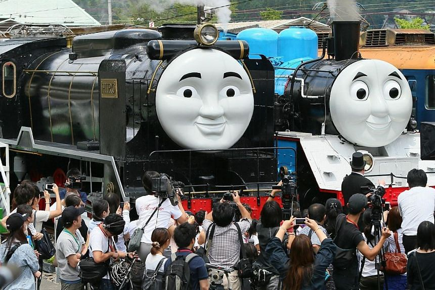 Life-sized Thomas the Tank Engine (right) and Hiro (left), surrounded by the media, at Senzu station on Japan's Oigawa railway, in the town of Kawanehon in Shizuoka prefecture, west of Tokyo on July 2, 2014. -- PHOTO: AFP