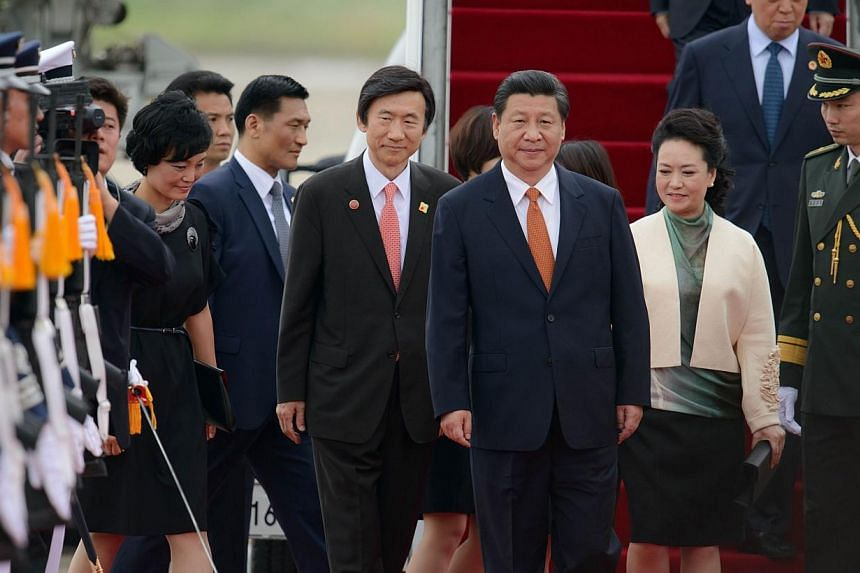 China's President Xi Jinping (centre) and his wife Peng Liyuan (second, right) are welcomed after disembarking from their aircraft upon arrival at Seoul Air Base on July 3, 2014. Mr Xi arrived in Seoul on Thursday, July 3, 2014, for a state visit see