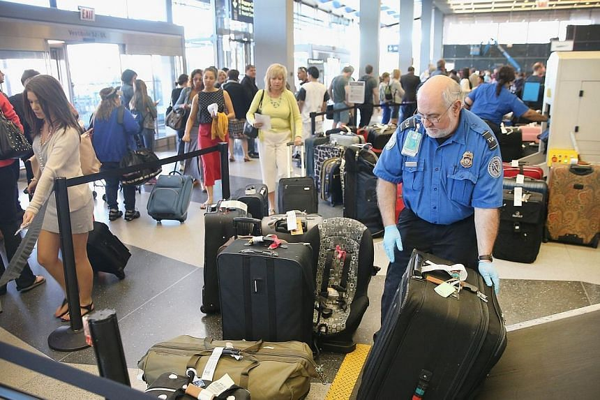 A TSA agent checks luggage as passengers arrive for flights at O'Hare International Airport on May 23, 2014 in Chicago, Illinois.US authorities plan to bolster security at some airports in Europe and the Middle East with direct flights to the U