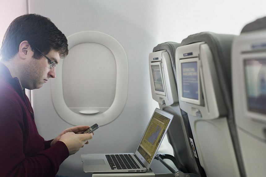A man uses his mobile phone on a flight out of John F. Kennedy International Airport in New York in 2013. Airlines with direct flights to the United States have been told to tighten screening of mobile phones and shoes in response to intelligence rep