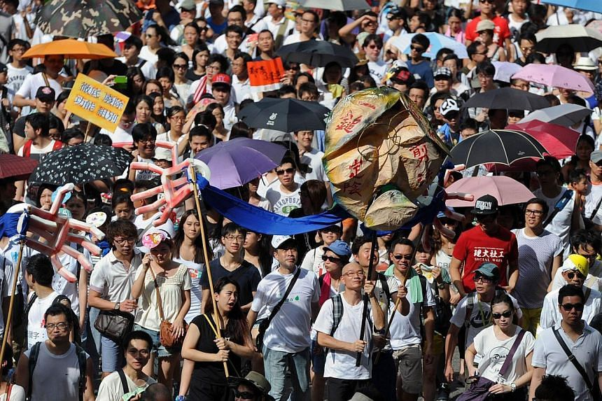 Protesters marching during a pro-democracy rally seeking greater democracy in Hong Kong. China's top newspaper on Friday dismissed fears that the autonomy of the former British colony of Hong Kong was being eroded, saying Beijing's policy had not and