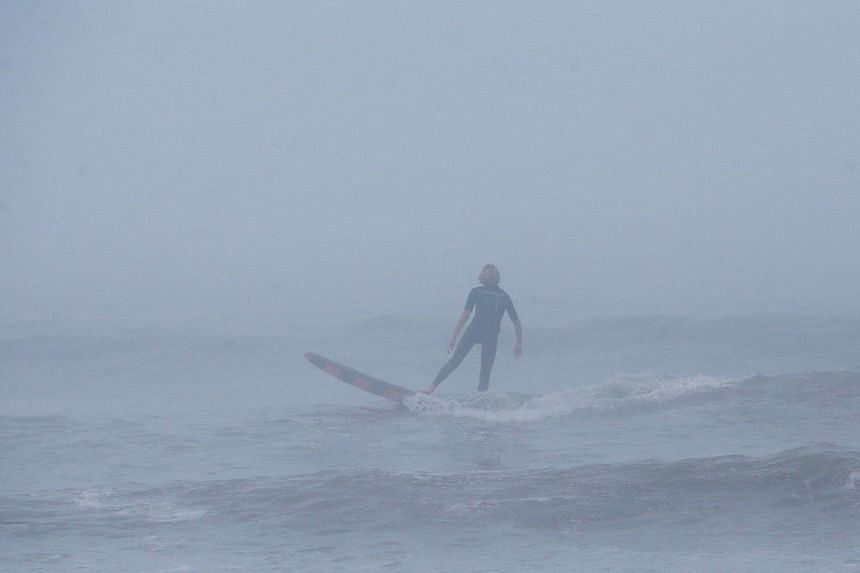 A man surfs in the fog as strong winds and heavy surf from Hurricane Arthur begin to roll in, on July 3, 2014 in Nags Head, North Carolina. Hurricane warning has been issued for North Carolina's Outer Banks due to approaching Hurricane Arthur. -- PHO