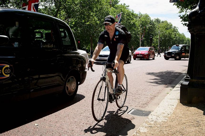 A cyclist rides on the Mall in central London on July 3, 2014. Once a niche sport, cycling has become so popular in Britain that it has spawned a new breed of fans who would rather buy a bike than a Ferrari and who confront their expanding waistlines