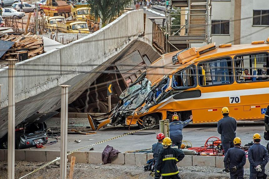 Firefighters and policemen work at the site where several vehicles were crushed by a viaduct that collapsed in Belo Horizonte, Brazil, on July 3, 2014. The collapse killed at least two people, emergency officials said. -- PHOTO: AFP