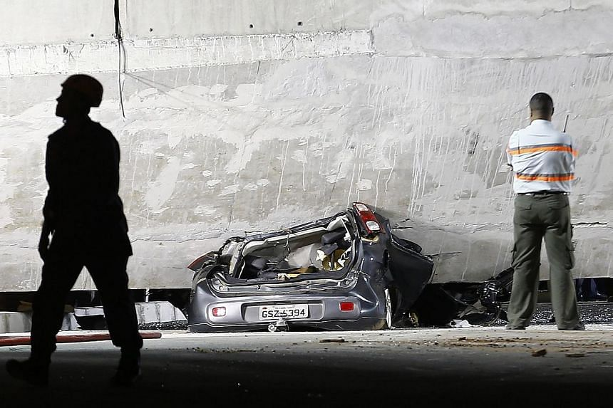 A car is trapped underneath a bridge that collapsed while under construction in Belo Horizonte on July 3, 2014.Rescue workers pulled a body from the wreckage of a collapsed highway overpass in the Brazilian World Cup host city of Belo Horizonte