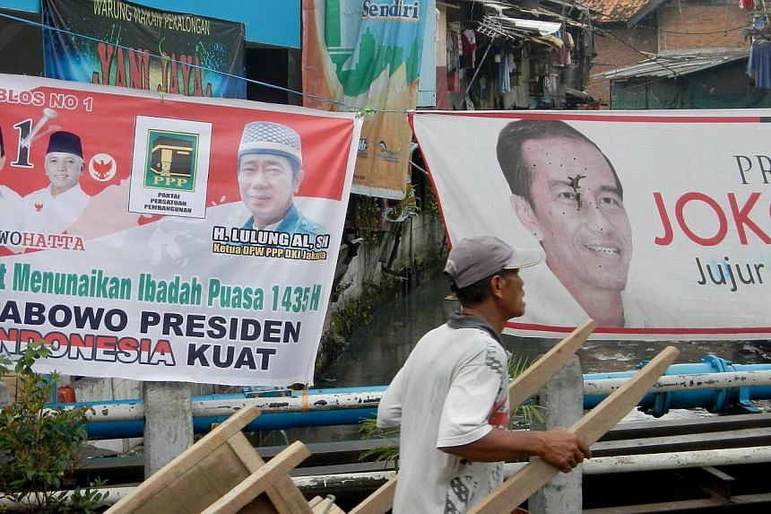 An Indonesian man pulls his cart past both presidential election candidates' banners, Joko Widodo (right) and Prabowo Subianto (left), in Jakarta on July 3, 2014 prior to July 9 vote.Indonesia's General Elections Commission (KPU) has released t