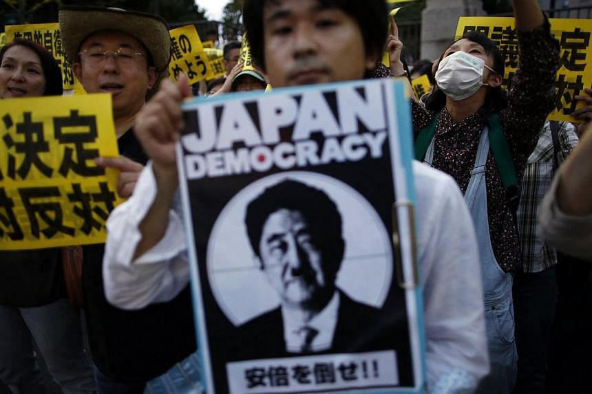"Protesters gather at a rally against Japan's Prime Minister Shinzo Abe's push to expand Japan's military role in Tokyo. On July 1, the Japanese Cabinet decided to ""reinterpret"" its post- World War II pacifist Constitution by allowing the right to col"