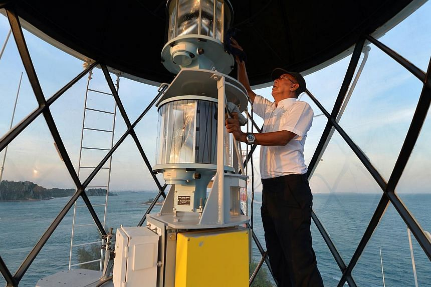 Lighthouse keeper Syed Hassan Syed Agil Al-Yahya at the top of the Raffles Lighthouse earlier this year (top). The lighthouse above The Fullerton Hotel is among two decommissioned ones here. Visitors will get the rare chance to climb Raffles Lighthou