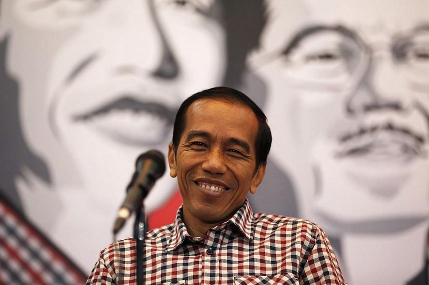Presidential candidate Joko Widodo smiles during a news conference in Bandung on July 3, 2014. Presidential candidate Widodo plans to go to Saudi Arabia for a minor haj or umrah during the quiet period to seek God's blessing ahead of the electio