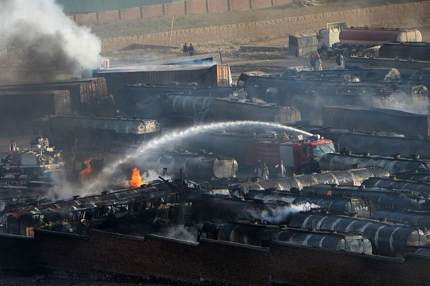 Afghan firefighters attempt to extinguish burning fuel trucks following an overnight attack by Taleban militants in Chawk-e-Arghandi on outskirts of Kabul on July 5, 2014.-- PHOTO: AFP
