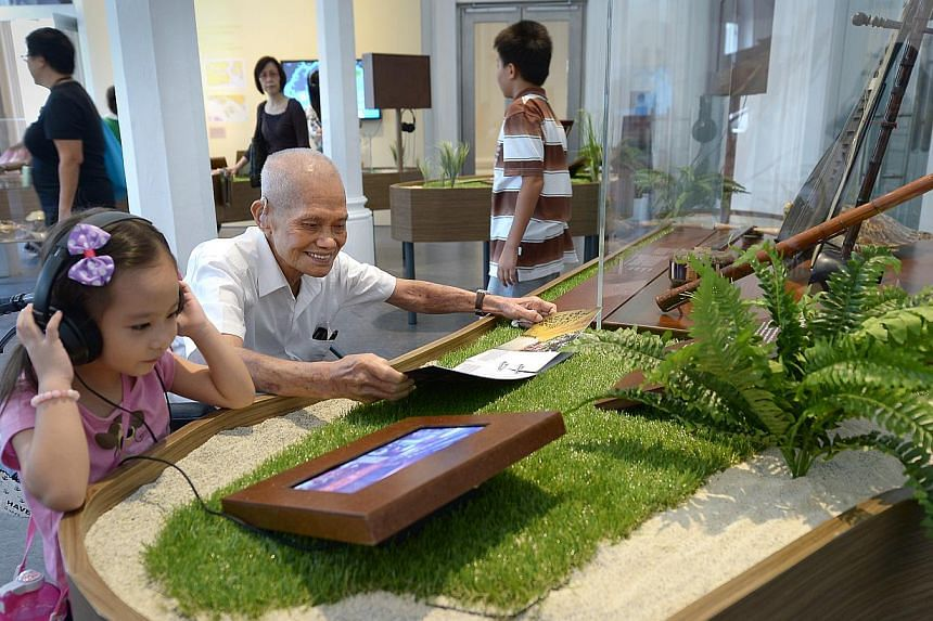 Mr Lee Pok Sew, 83, and his granddaughter Ariel, four, enjoying an exhibit on Kusu Island during a visit to the National Museum. The museum will be one of the 11 hubs for this year's HeritageFest.