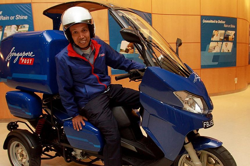 Postman Kamarol Zamal Atan, 50, sitting on SingPost's new second-generation three-wheeler. Sixty such vehicles, which can hold more parcels, will be deployed in the next three months to help postmen with their loads. -- ST PHOTO: LAU FOOK KONG