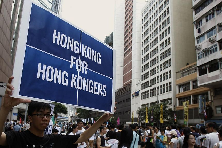 A protester carries a placard during a mass protest demanding universal suffrage in Hong Kong on July 1, 2014. -- PHOTO: REUTERS